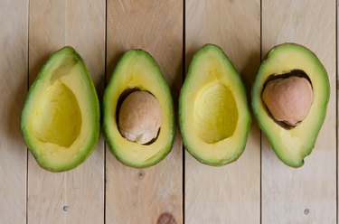 Four halves of avocados on wood background