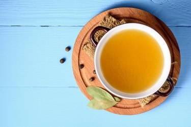 Chicken broth in ceramic bowl on blue wooden background.