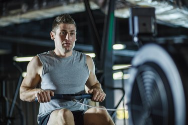 Mid adult male athlete concentrating while rowing at the gym