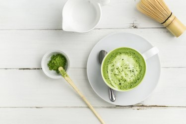 Green tea matcha latte cup on white background from above flat view.