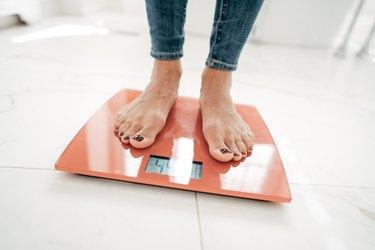 A woman's feet on an orange scale in a white bathroom