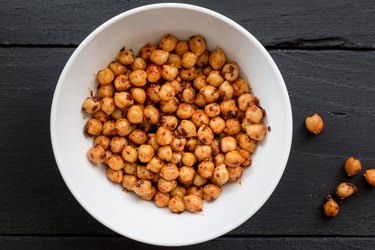 Chickpeas with spice in bowl on black background close up top view image