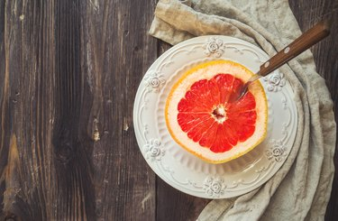 Half a grapefruit on vintage plate with spoon