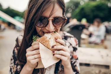 A stylish young woman eating a large turkey burger outside