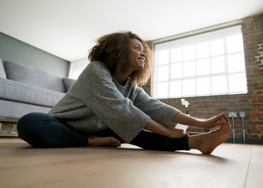 woman stretching as part of a productive morning routine