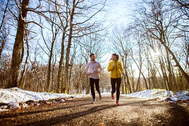 Young sporty happy couple jogging in sportswear through the forest in the sunny winter morning.