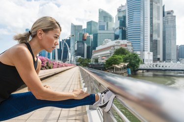 portrait of young Asian woman doing stretching before running in city