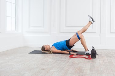 Side view of woman in sportswear with resistance bands training weak glutes