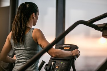 Athletic woman exercising on cross trainer in a health club.
