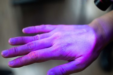Hands under black UV light to detect glow in the dark germs around nails and fingerprint as visual tool for teaching proper handwashing, aseptic techniques, and general infection control