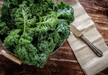 Kale in basket and knife on wooden  background top view on daylight superfood vegetables