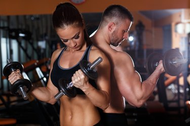 Fitness couple lifting dumbbell in the gym.