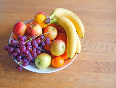 close up of bowl of fruit with bananas and grapes on wooden table