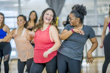 Two women dancing together in a group class at a gym