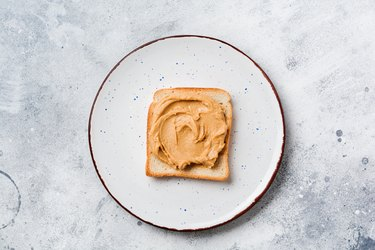 Toast with peanut butter and banana slices on an old gray concrete background. Top view.