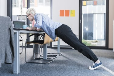 Woman in office doing push-ups on desk