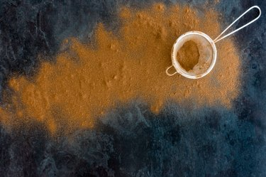 Cinnamon Powder in Sieve and on Blue Marbled Background