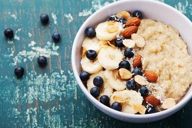 Bowl of homemade oatmeal porridge with banana, blueberries and almonds