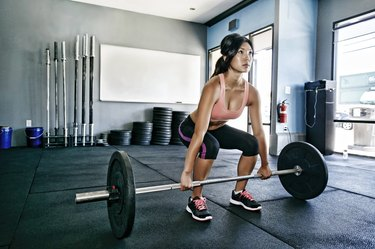 Asian woman strengh training at the gym