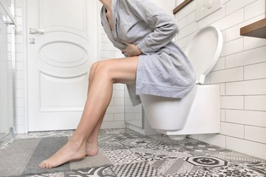 Woman sitting on toilet holding her stomach