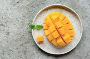 Sliced mango fruit on plate.