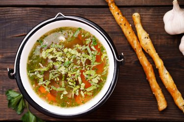 Homemade chicken vegetable soup on wooden table