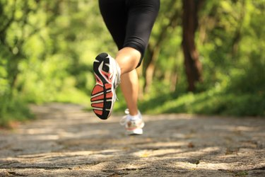Runner athlete legs running on forest trail.