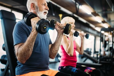 Fit senior man and woman doing exercises in the gym to combat belly fat and weight gain