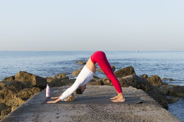 Young woman practicing yoga on the beach, doing downward facing dog