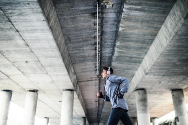 Young sporty man with headphones running under a concrete bridge in the city.