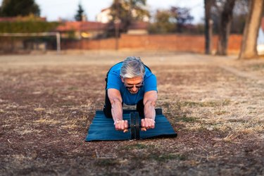 Senior doing workout with ab roller outdoors