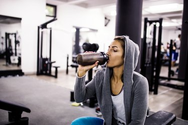 woman drinking a protein shake after a workout in the gym