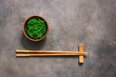 Wakame Chuka or seaweed salad with sesame seeds in bowl on dark brown rustic background. Traditional Japanese food. Top view, flat lay,copy space.