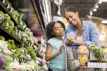 Mother and daughter grocery shop together using list