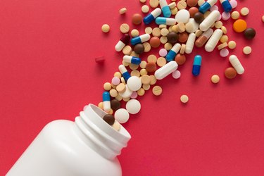Group of assorted colorful tablets. Capsules spilling out of white bottle.