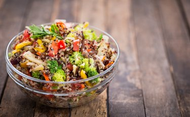 Quinoa and vegetable salad in a glass bowl on a wooden table