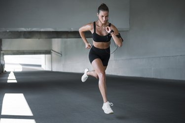 Young sportswoman running outdoors through concrete tunnel