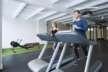 Man and woman running on treadmill at gym