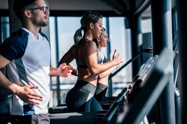 Side view of fit young man and women running side by side on treadmills at the gym.