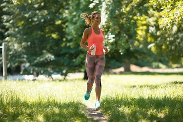 Young woman jogging outdoor at the park on beautiful summer day.
