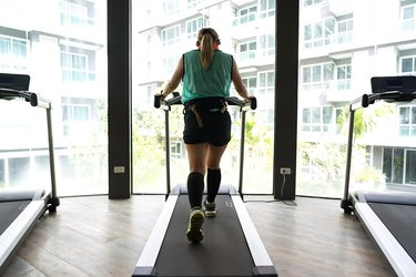 Asian woman wearing calves compression walking on treadmill