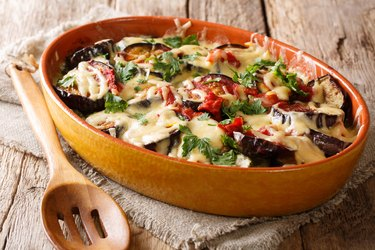 healthy vegetarian slow cooker recipes like baked eggplants with tomatoes, herbs and cheese close-up in a baking dish. horizontal