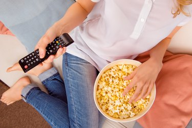 Close up of woman eating popcorn with remote control tv