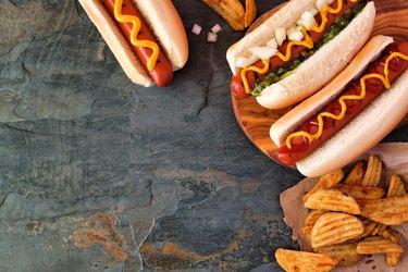 Hot dog corner border, overhead view on a dark stone background