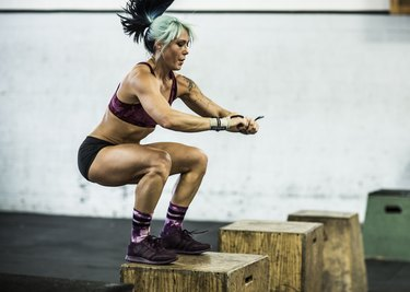Woman doing box jumps during AMRAP workout at a CrossFit gym