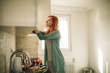 Redhead woman searching for something in kitchen cabinet.