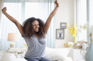 Black woman stretching on bed