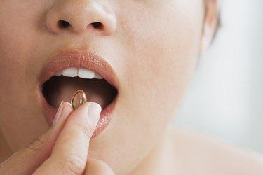 Close up of Hispanic woman taking vitamin