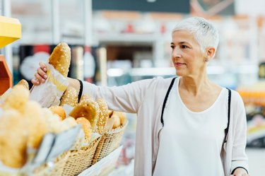 Mature Woman Groceries Shopping for foods for gluten free symbol