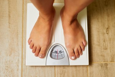 Female bare feet on weight scale in a bathroom
